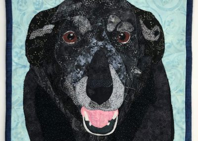 fabric wall hanging of black dog