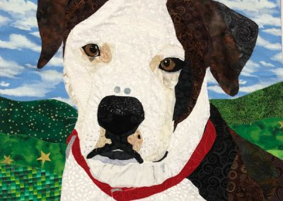 pet portrait: brown and white dog with hills and sky