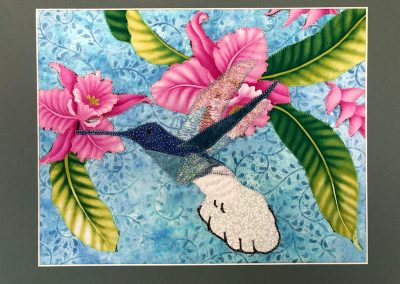 fabric picture of a hummingbird and bright flowers