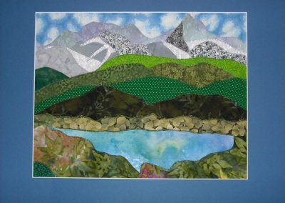 fabric wall hanging of lake and mountains