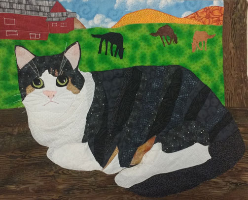 fabric picture of a cat and a barn