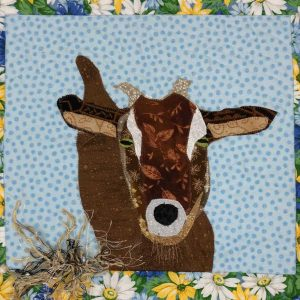 closeup of brown goat and fabric hay on fabric wall hanging art piece