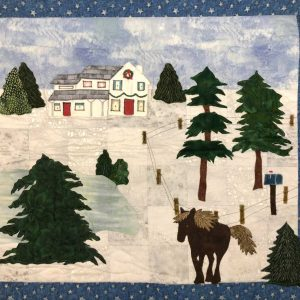 large fabric wall hanging depicting winter scene with horse, pine trees, and country house