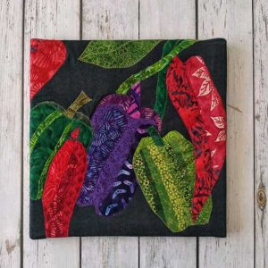 Green, red, and purple fabric peppers on canvas art