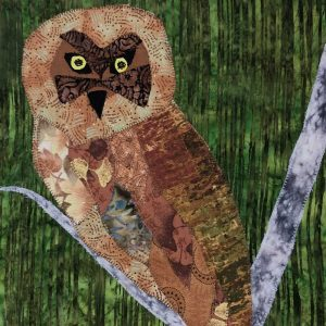 matted fabric art piece of a brown owl in the forest
